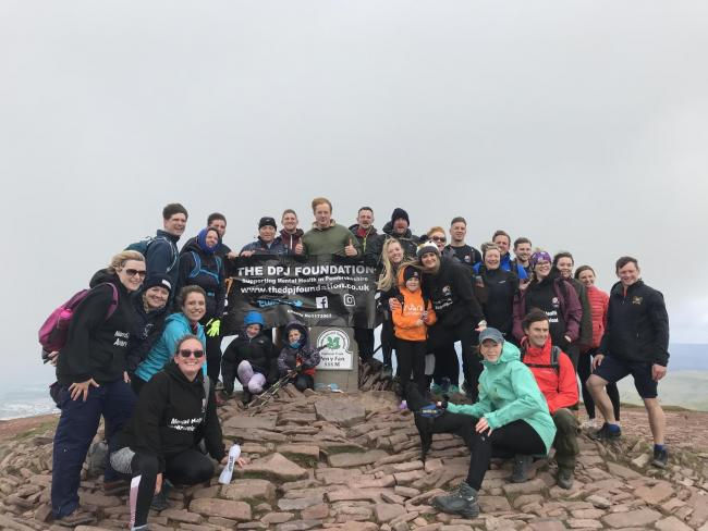 Matt Launder, Dan Launder, George Collins and Gareth Owen pictured with friends, family and supporters after completing the Nine Peaks Challenge on Pen y Fan on June 16.