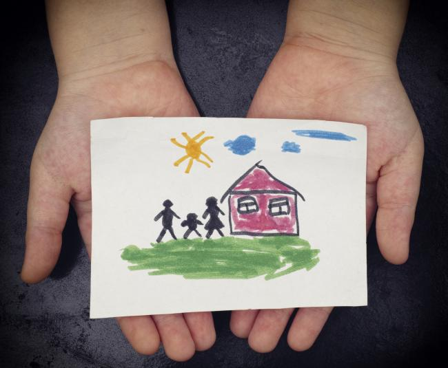 Child holds a drawn house with family. Picture: Getty