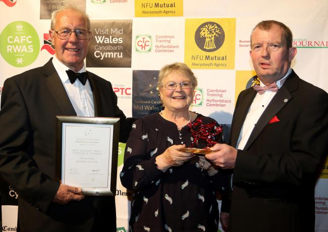 George (left) and Katie Barstow from Fforest Fields, Hundred House, receive the Best Holiday Park, Camping and Touring Award from Dylan Roberts, managing director of sponsor Salop Leisure, at the Mid Wales Tourism Awards held at The Hafren, Newtown. Pictu