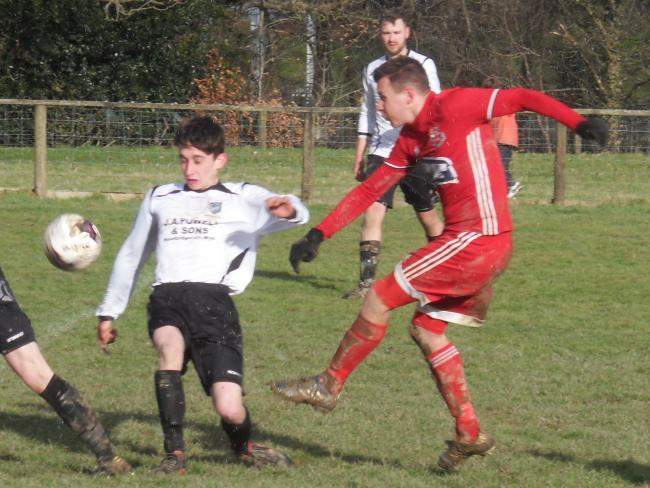 Knighton Town goal scorer Mark Jones (red shirt) has a shot on target against Newbridge-on-Wye. Photo: Stuart Townsend.