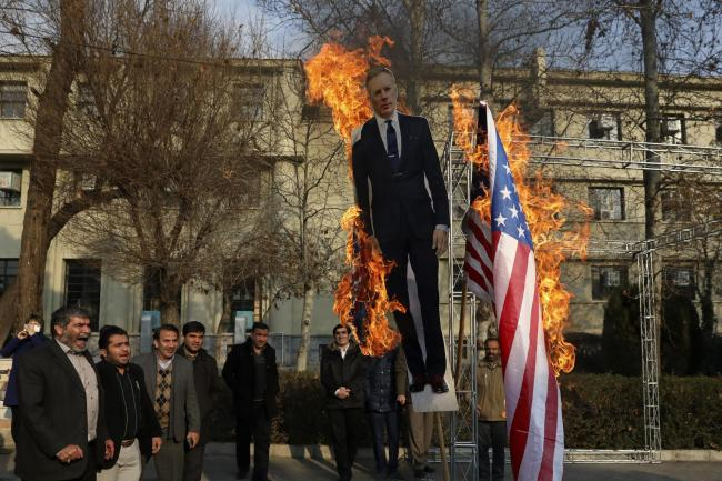 Pro-government protesters set fire to US and British flags with a life-size cut-out of Britain's ambassador to Tehran Rob Macaire in Tehran