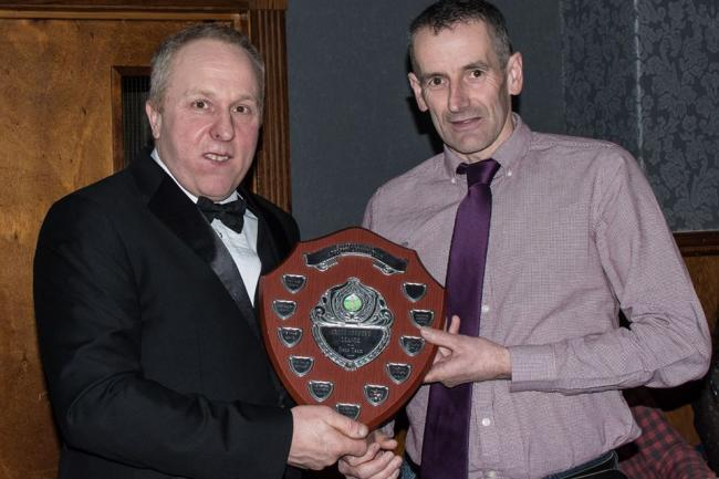 Builth Wells Running Club's Christian Prynne presents the 2020 Herefordshire Cross Country League shield to Mike Pfeiffer.