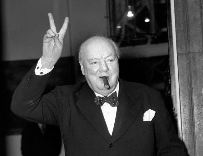 Sir Winston Churchill giving his familiar 'V' sign.