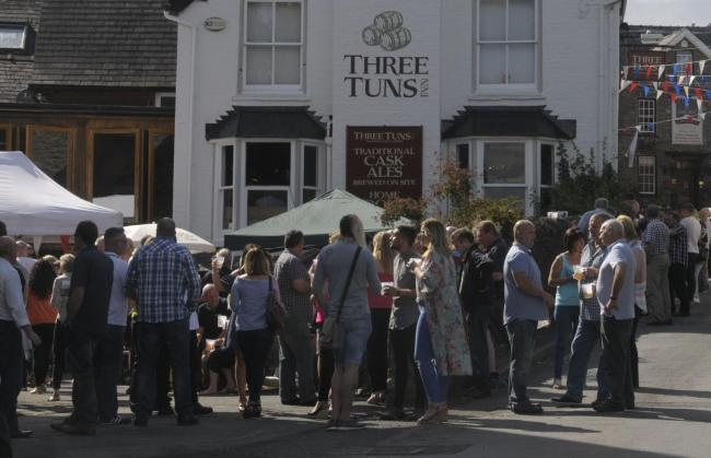 Visitors to the beer festival enjoys themselves in and.. around the Three Tuns in Bishops Castle..