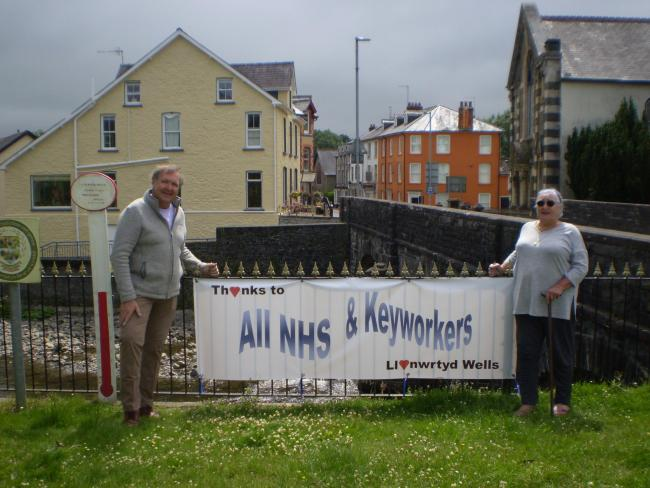Town councillors Peter James and Lynda Pace-Avery unveil the banner thanking the NHS and key workers on behalf of Llanwrtyd Wells.