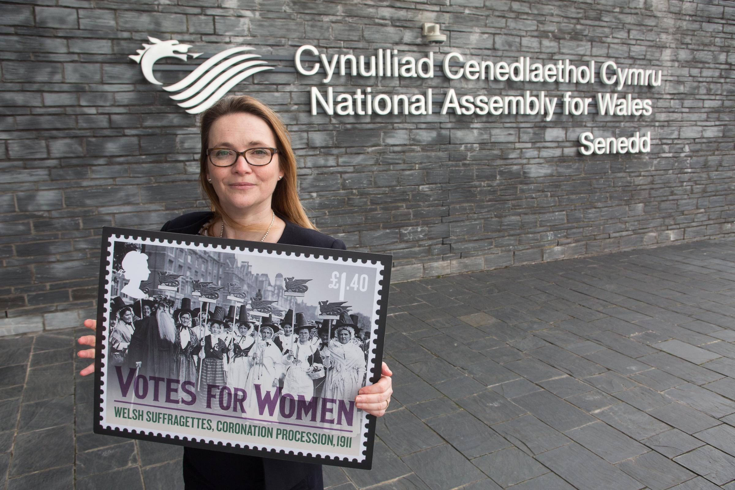 Kirsty Williams, Cabinet Secretary for Education holds the newly designed stamp celebrating women's vote at The Sennedd, Cardiff Bay.