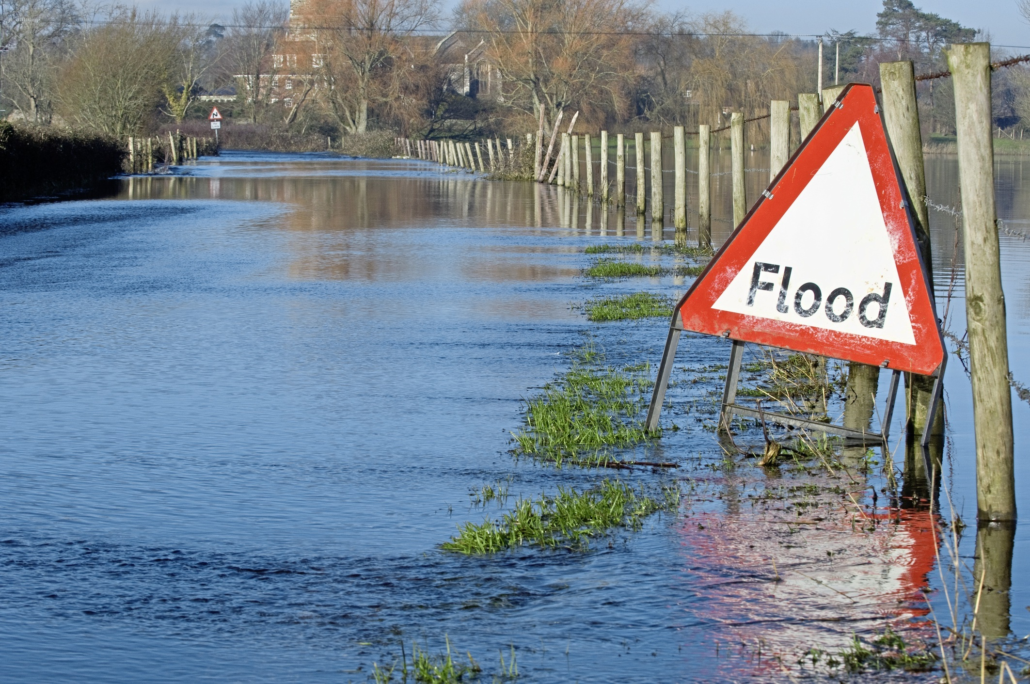 A flood warning sign, on a closed country road next to water logged fields in the Avon Valley, Hampshire, England. Flooded after an extreme amount of rainfall at the start of 2014.
