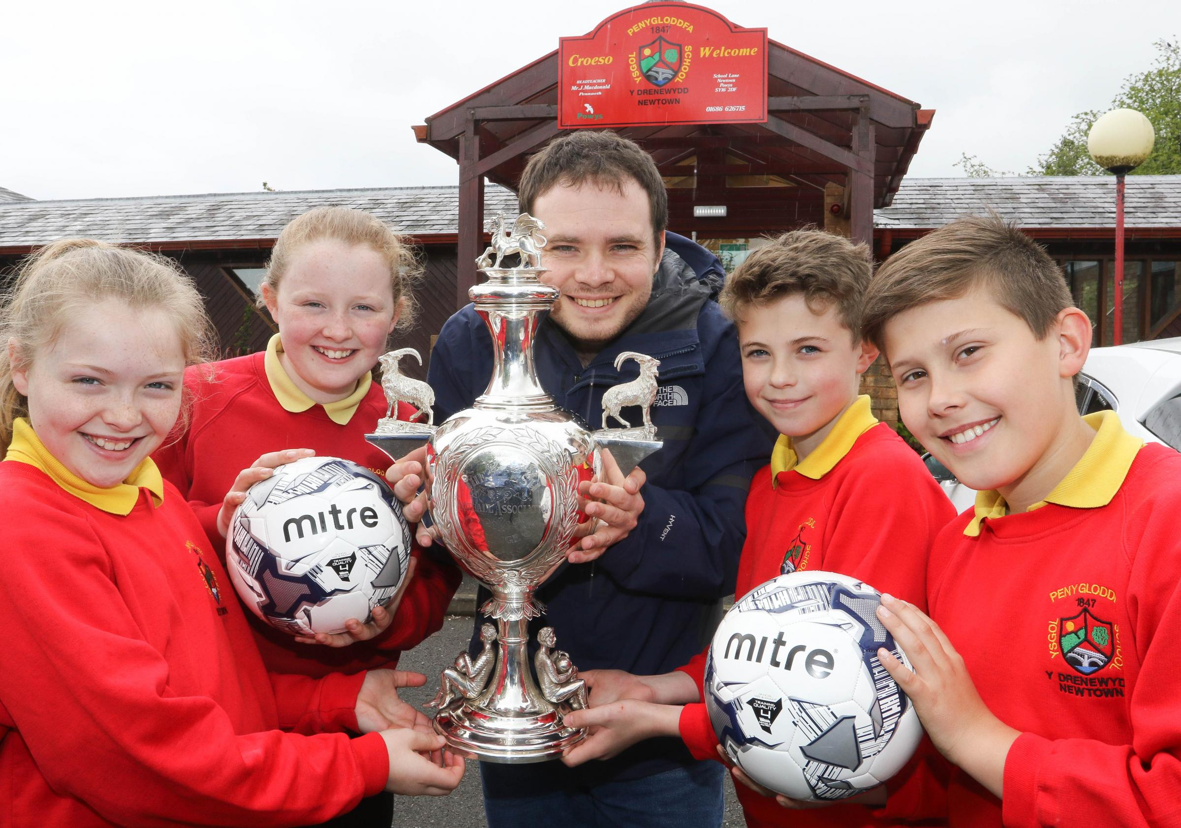Penygloddfa Primary school FAW coaching session and the Welsh Cup on display..pictured from left, Macy Farrington (10) Halle Trigg (11) Matthew Close (FAW) Griff Davies (10) and Joe Morgan (11).Picture by Phil Blagg.PB226-2018-3.