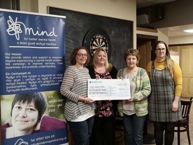 Ria Claridge, Brenda Claridge and Lisa Griffiths hand the cheque for £4,539.22 to Jo Houlsby of Mid Powys Mind.