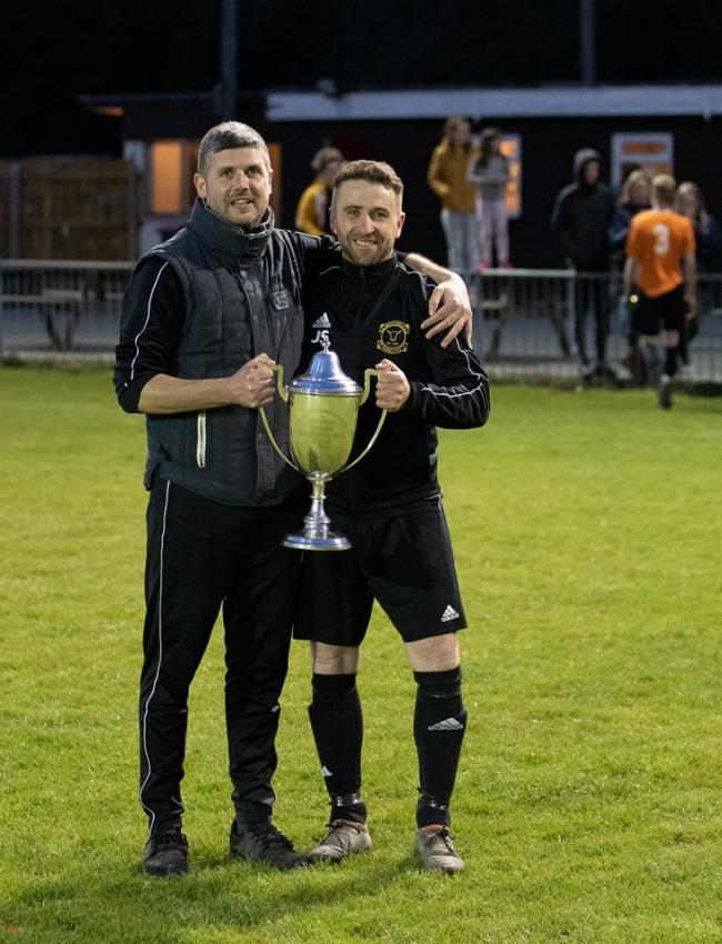 Builth Wells manager Dylan McPhee and assistant Jason Samuel with the MMP-NL Mid Wales League Cup final trophy following their side's 2-1 extra-time win over Caersws in Rhayader on Saturday. Picture by Darren Laurie.